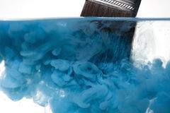 Cleaning a paint brush. Viewing a loaded paintbrush being submerged into water with the paint beginning to disperse Royalty Free Stock Photo