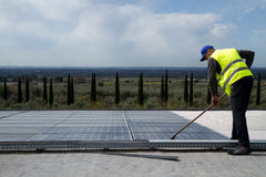 Cleaning panels. Laborer cleaning photovoltaic panels on a roof Stock Photo