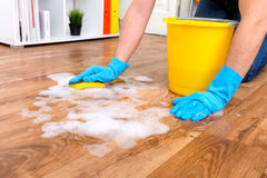Cleaning a parquet floor with foam stock image