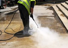 Cleaning the pavement of the street with pressurized water. Municipal worker cleaning street sidewalks with hot pressurized water Royalty Free Stock Photography