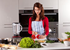 Cleaning the pepper. Pretty young woman cleaning the pepper in the kitchen Royalty Free Stock Photos
