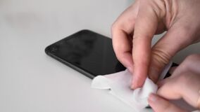 Cleaning phone screen with antibacterial wipe. Covid-19 virus spread prevention. Personal modern hygiene
