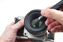 Cleaning photographic lens from dust with brush Stock Photos
