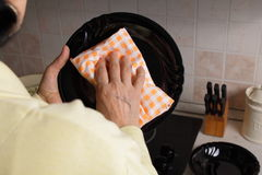 Cleaning plates in the kitchen. Elderly woman cleaning black ceramic plate with a dishcloth, in the kitchen Royalty Free Stock Photo