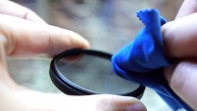 Cleaning the polarizing filter for the camera. Cleaning of the polarizing filter for the camera care of photographic equipment stock footage