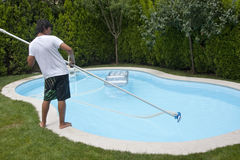 Cleaning the Poll. A boy is vacuuming the backyard pool Royalty Free Stock Photos
