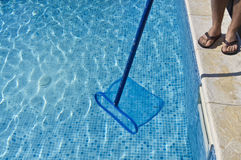 Cleaning pool. A men cleaning the pool and the water seams very bright Stock Photo