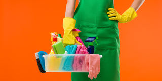 Cleaning in progress. Close-up of cleaning lady holding supplies, on orange background stock images