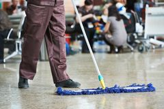 Cleaning public hall floor. Cleaner with mop and uniform cleaning hall floor of public business building Royalty Free Stock Photos