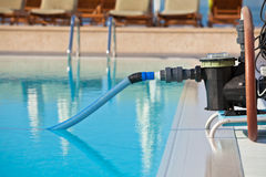 Cleaning pump working with a swimming pool Stock Photography