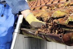 Cleaning a rain gutter. Man Cleaning a rain gutter in Close up Royalty Free Stock Photos