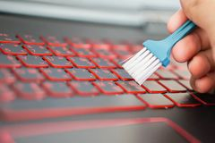 Cleaning red - black style keyboard with blue cleaning brush royalty free stock photography