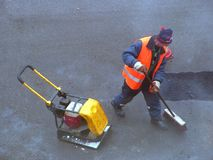 Cleaning the road. Road mender at work; hard work, power, blue-collar concept stock photos