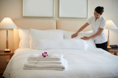 Cleaning room. Maid cleaning bedroom after guests, focus of clean towels Royalty Free Stock Images