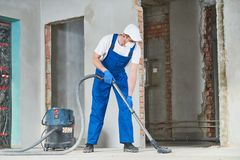 Cleaning service. dust removal with vacuum cleaner. Service man cleaning and removing construction dust with vacuum cleaner after repair royalty free stock image