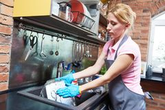 Cleaning service. woman washing dishes at kitchen. Cleaning service. Female staff worker clean kitchen. Washing plates in sink Royalty Free Stock Images