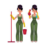Cleaning service girl in overalls holding mop, bucket, washing windows Royalty Free Stock Image
