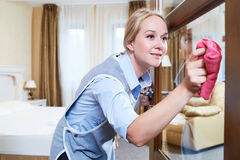 Cleaning service. hotel staff clean glass door from dust Stock Images