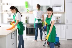 Cleaning service team working. In kitchen Royalty Free Stock Images