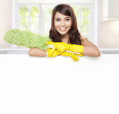 Cleaning service woman presenting blank board. Cleaning service woman presenting a blank board and hold a duster Stock Images