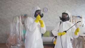 Cleaning service workers or scientists in protective overalls dancing