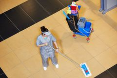 Cleaning services. Female cleaner with mop and uniform cleaning hall floor of public business building Royalty Free Stock Image
