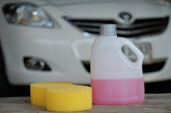 Cleaning shampoo and sponge on car background stock images