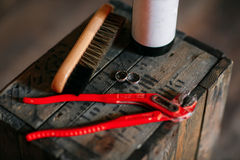 Cleaning shoes on wooden background. black shoe with a brush. Red adjustable wrench. Wedding rings. beer bottle. Wood Stock Images