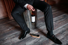 Cleaning shoes on wooden background. black shoe with a brush. Red adjustable wrench. Wedding rings. beer bottle. Wood Stock Image