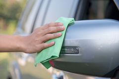 Cleaning side mirror car. Hand with green microfiber cloth, cleaning side mirror car Stock Image