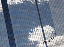 Cleaning skyscraper windows. Cloudscape reflected on modern glass skyscraper with silhouetted team on workers cleaning windows Stock Image