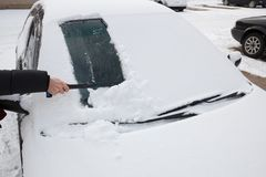 Cleaning snow from car Stock Images