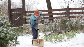 Cleaning snow in the winter near the house. The child cleans shovel the snow covered track. Boy removes snow shovel near the house. Cleaning snow in the winter stock footage