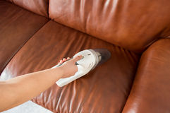 Cleaning sofa with vacuum cleaner Stock Image