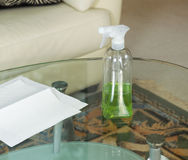 Cleaning Solution Spray Bottle on Top of Dirty Glass Table Royalty Free Stock Images