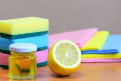Cleaning sponge with scrub and rags set, olive oil in glass jar, lemon half on a wooden table. Eco house cleaning set. Closeup Stock Image