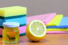 Cleaning sponge with scrub and rags set, olive oil, lemon on a wooden table. Eco house cleaning concept. Closeup. Cleaning sponge. Cleaning materials. House Royalty Free Stock Images