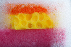 Cleaning sponge with soap foam on top. colorful violet orange yellow Macro view bubble suds, gray black background. Stock Image