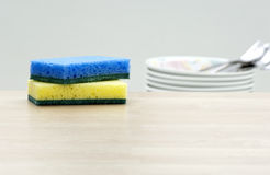 Cleaning sponges and dishes in a kitchen. Empty space on a wooden table with kitchen utensil, cleaning sponge and dishes (for message or product stock photography