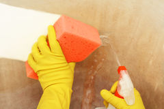 Cleaning with spray. Cleaning a very dirty surface with spray and sponge Royalty Free Stock Photos