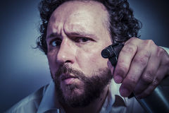 Cleaning spray, man with intense expression, white shirt Royalty Free Stock Images