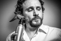 Cleaning spray, man with intense expression, white shirt Stock Photos