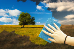 Cleaning for spring. Hand cleaning window, turning dark landscape into colorful spring view stock photo