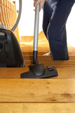 Cleaning the stairs. A person caught while cleaning the wooden stairs whit a vacuum cleaner Stock Image