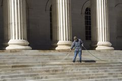 Cleaning the stairs. A Denver city worker spraying the steps of the Colorado Supreme Court Building. Can be used to illustrate cleaning up the justice system royalty free stock image