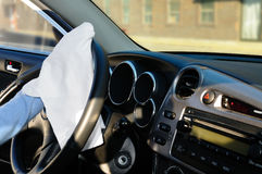 Cleaning steering wheel. Woman's hand with white rag cleaning car's steering wheel and front panel Stock Image