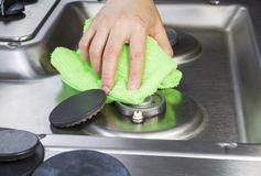Cleaning stove top with microfiber cloth Stock Images