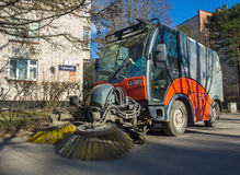Cleaning streets of the city with the help of subcompact sweeper Royalty Free Stock Photo