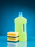 Cleaning supplies. Bottle of liquid detergent and sponges against blue background Royalty Free Stock Photos