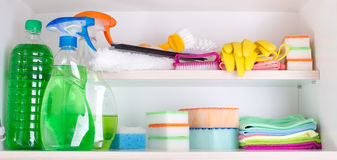 Cleaning supplies in pantry. Cleaning supplies and tools arranged on shelves in pantry stock image